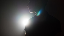 silhouette of a man standing in a spotlight