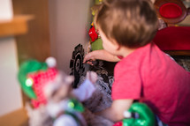 toddler playing with Christmas decorations