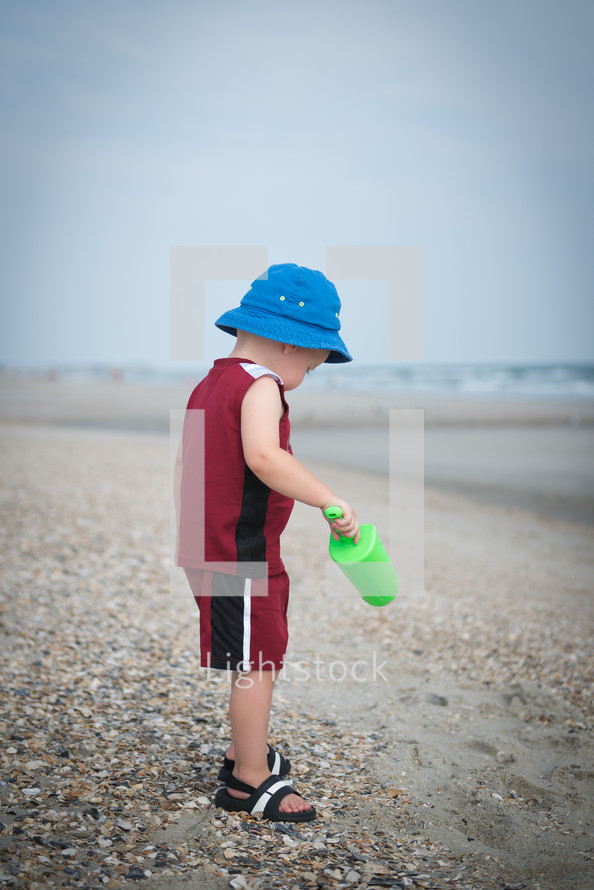 A little boy playing in the sand on a beach.