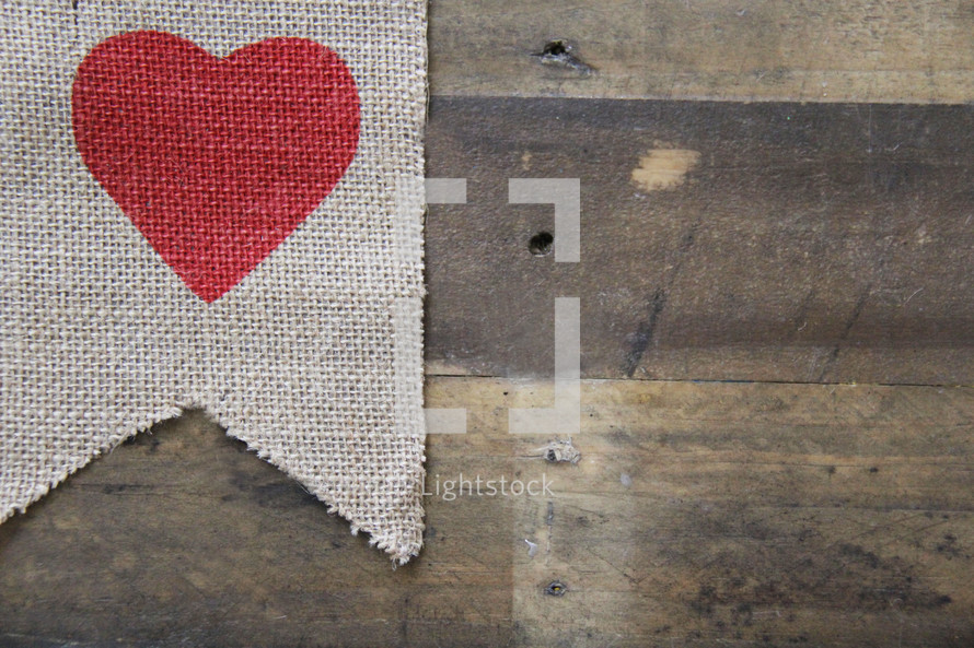 red heart on burlap on a wooden background