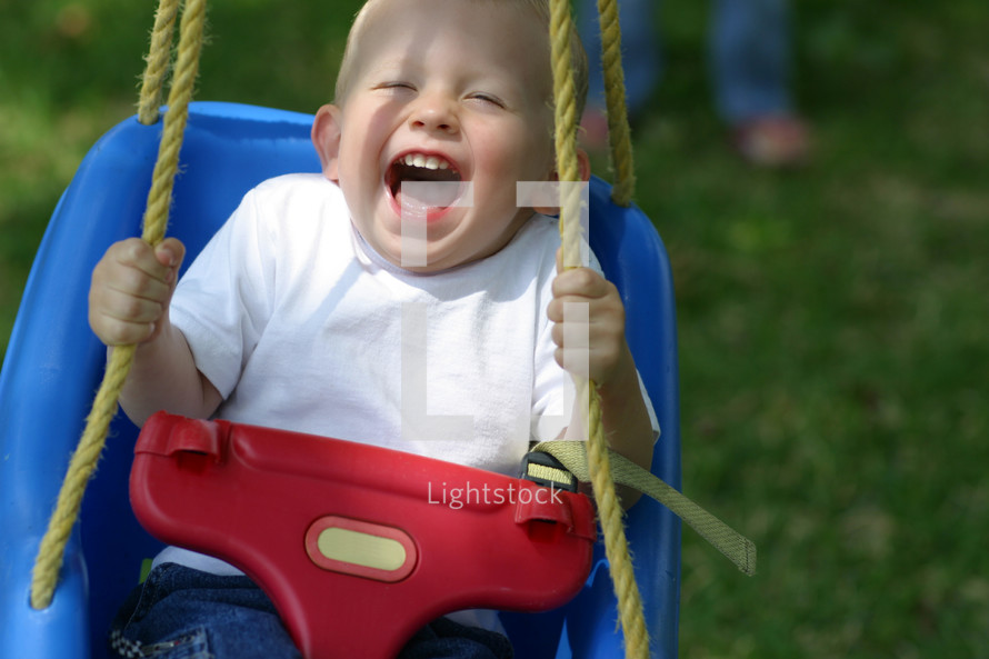 Boy toddler expressing pure chldlike joy as he swings from a tree in his yard with a parent in the far background watching.