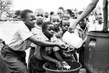 children washing hands with fresh water