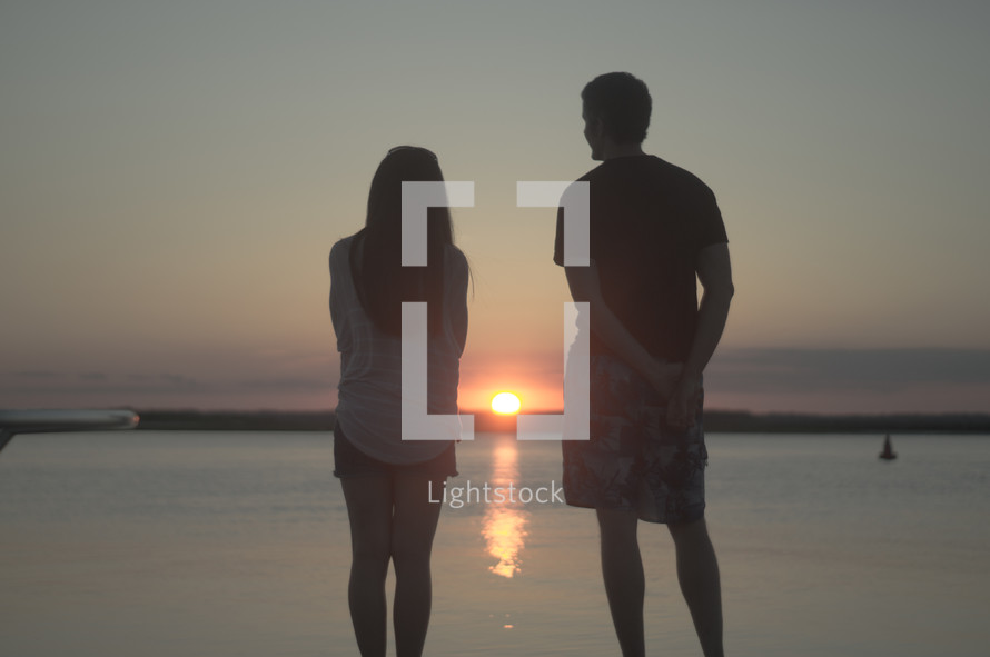couple watching a sunset over the ocean