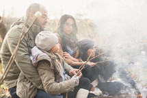 a family roasting marshmallows together