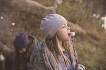 a girl child eating marshmallows off a stick