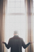 elderly man standing at a window with his arms outstretch in worship and praise to god