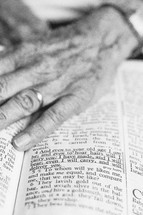 An elderly woman's hand on a Bible open to a passage about aging.