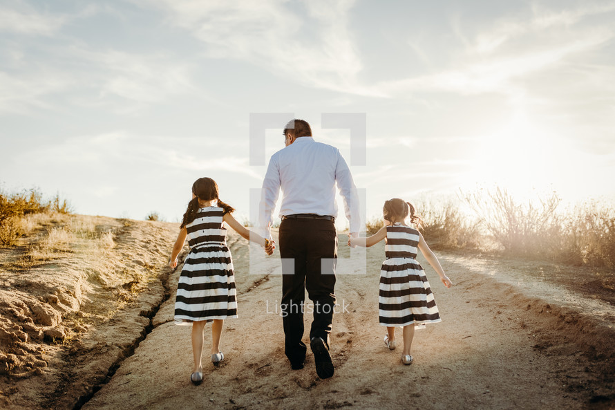 father walking up a hill holding hands with his daughter