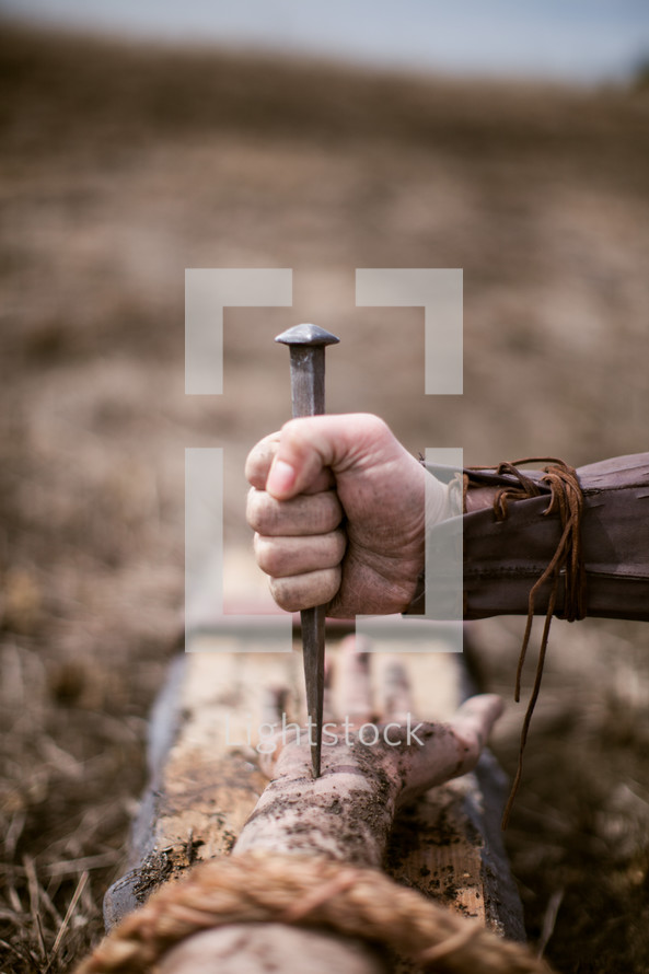 Roman soldier's hand holding nail on the cross.