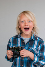 a happy young boy holding a camera