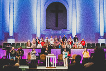 Choir singing on stage at church.