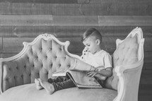 a boy child sitting on a couch reading a book