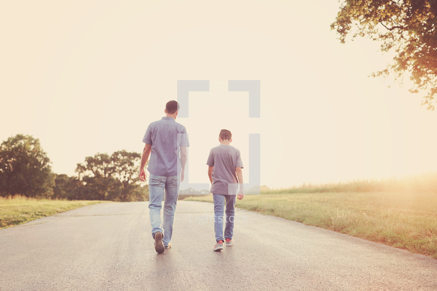 a father and son walking down a rural road together