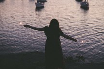 silhouette of a woman holding sparklers in front of water