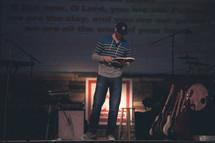 man reading a Bible at a contemporary worship service
