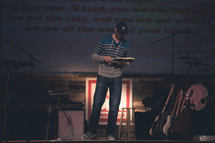 man reading a Bible at a contemporary worship service