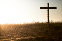 cross in a field at sunrise
