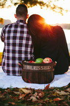 a woman with her head on a man's shoulder sitting on a blanket on the ground and a basket of apples with the word blessed