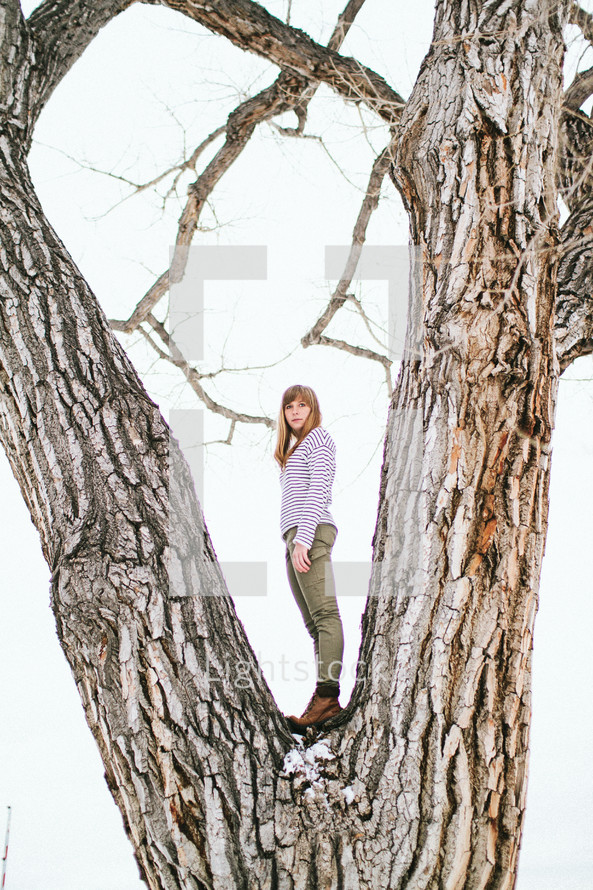 a woman standing in a tree