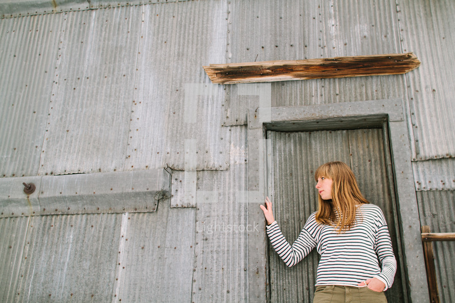 a woman standing in front of a sheet metal building