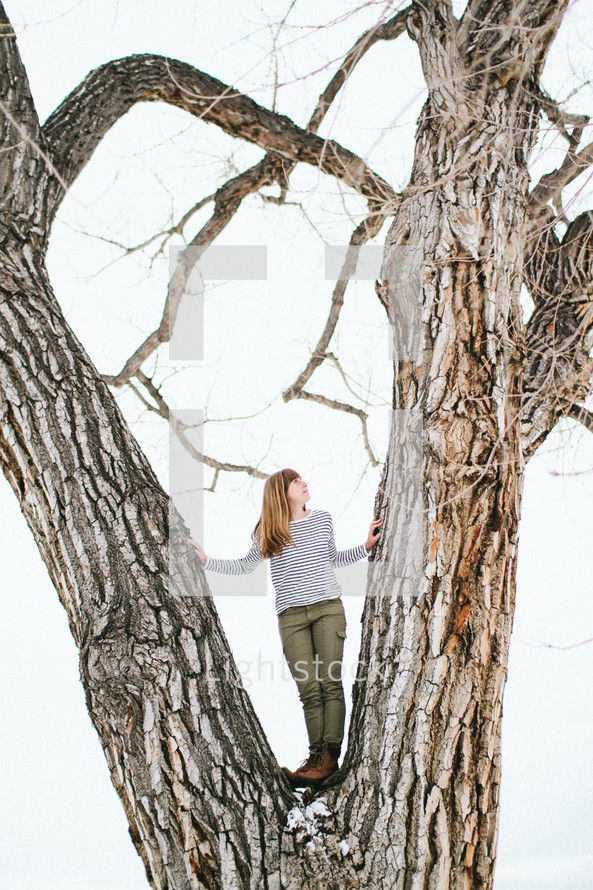 a woman standing between a tree