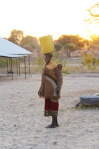 a woman with her baby carrying water on her head in a village