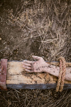 Jesus' arm tied to the cross.