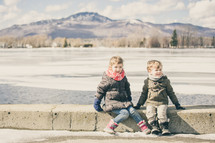 a boy and girl sitting on a curb in front of a frozen lake
