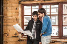 two men looking over blueprints