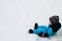 a toddler boy in a snowsuit sitting in snow