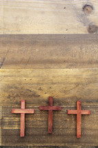 three wooden crosses on a wood floor