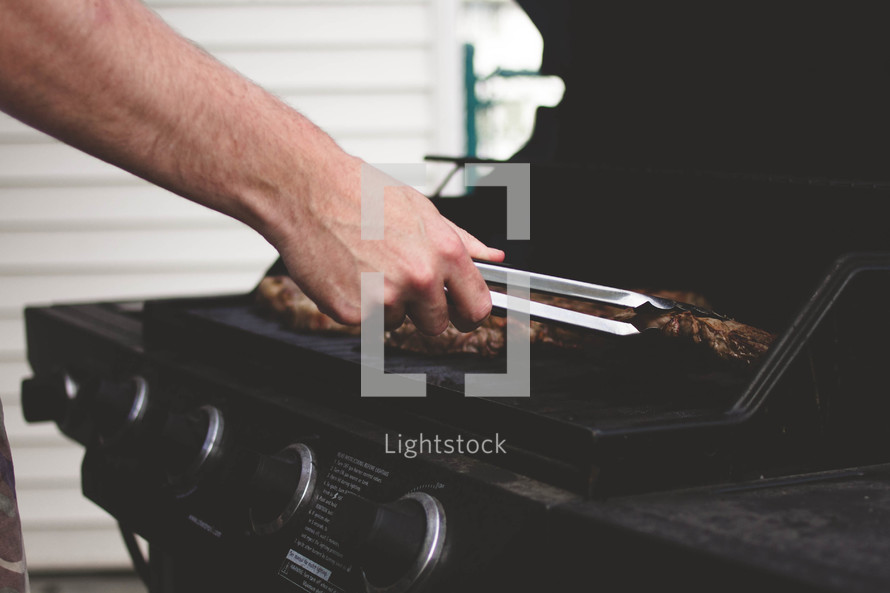 man flipping hamburgers on the grill