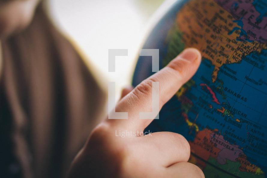 boy child pointing to a globe