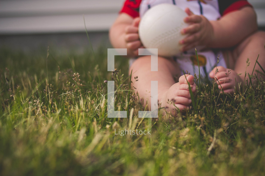 infant boy holding a baseball