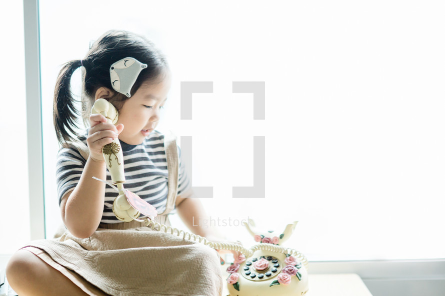 a little girl talking on a vintage phone