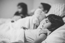 siblings lying in bed