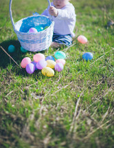 toddler playing with an Easter basket in the grass