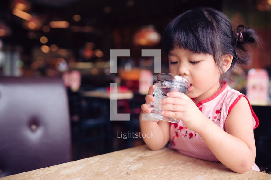 girl drinking water from a glass