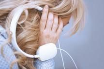 a woman holding headphones to hear ear