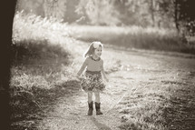 A little girl in a dress and cowboy boots outdoors.