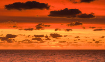 clouds in a red sky over the ocean at sunset