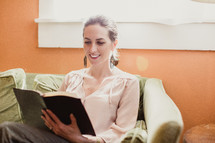 woman reading a Bible on the couch