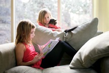 sister's reading a children's book together on a couch
