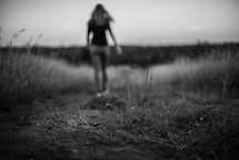 a woman walking down a worn path