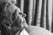 Light shining on the profile of an elderly woman.