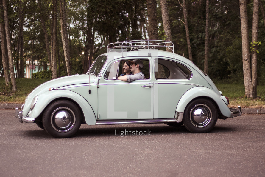 a couple driving in a vintage Volkswagen Beetle