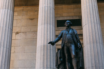 Statue of George Washington between white columns.