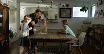 mother and children doing a science experiment in the dining room