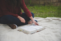 a teenage girl sitting on a blanket reading a Bible