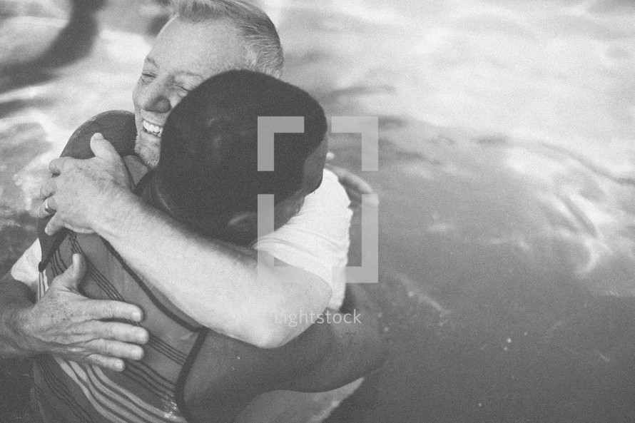 Two men hugging in a pool of water.